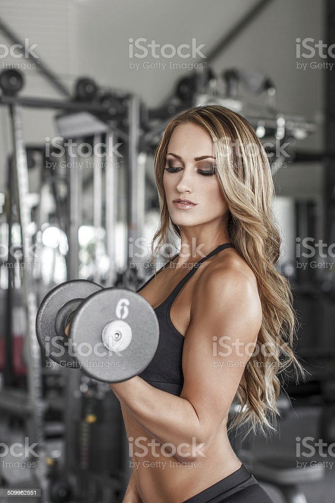 Fitness model pumping up muscles royalty-free stock photo
