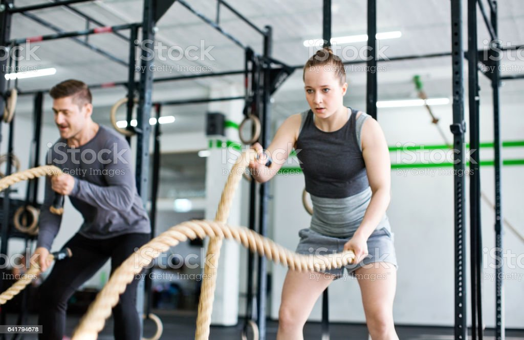 Fitness people exercising with battle ropes stock photo