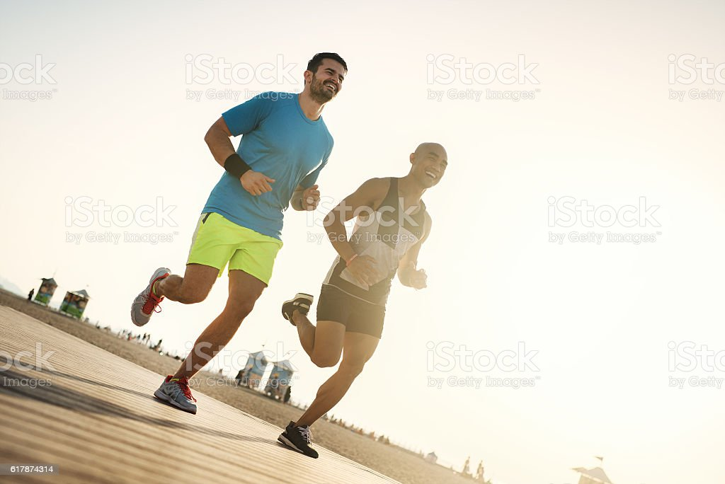 Fitness people running at the beach into the sunset. stock photo