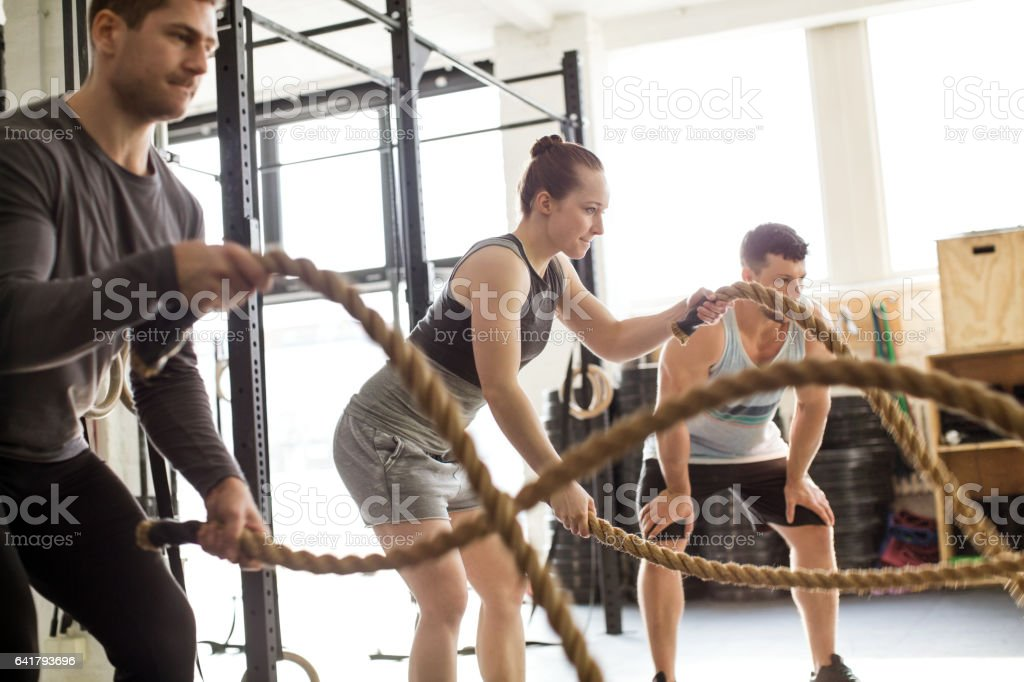 Fitness people working out with battle ropes at gym stock photo