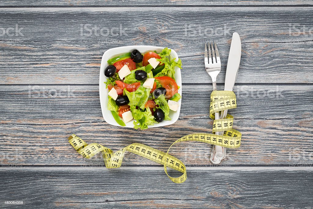 Fitness salad and measuring tape on wooden table. stock photo