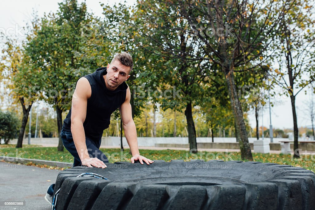Fitness sport man workout outdoor. with tractor tire. stock photo