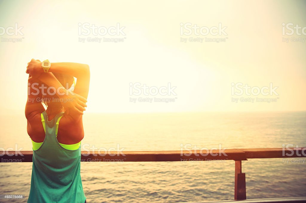 fitness sports woman stretching  on wooden boardwalk seaside stock photo