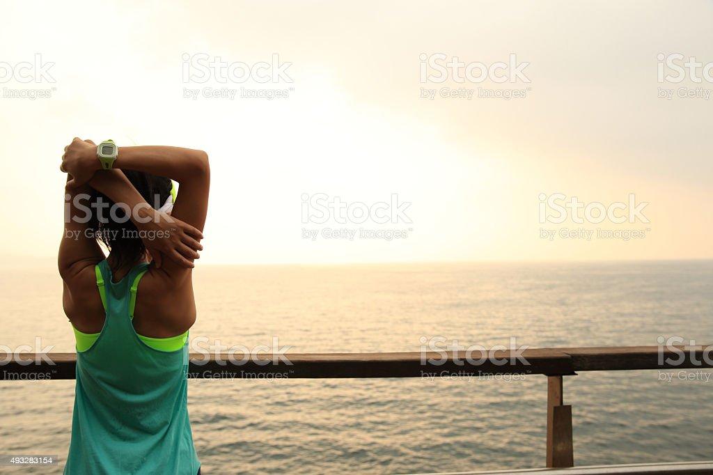 fitness sports woman stretching  on wooden boardwalk seaside stock photo