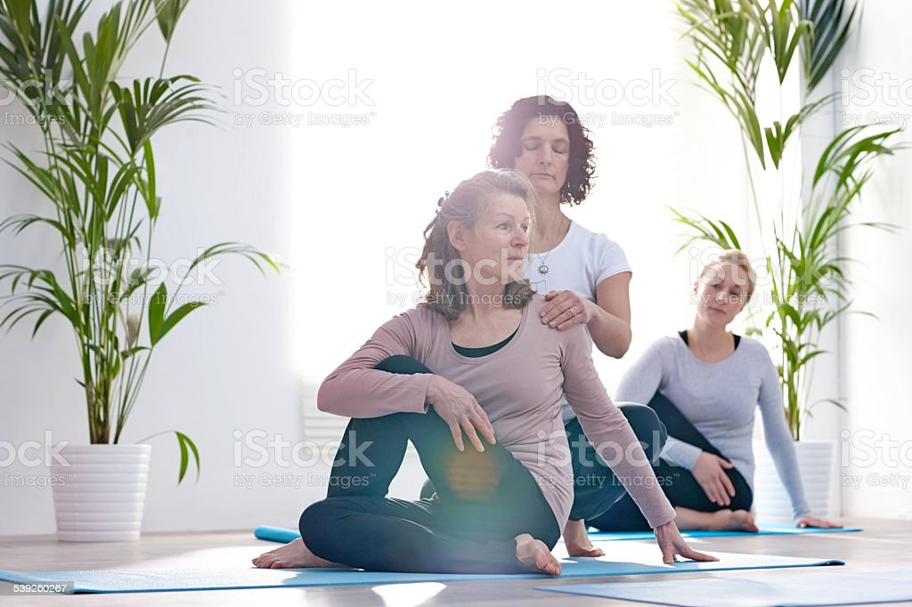Fitness trainer assisting woman with stretching workout stock photo