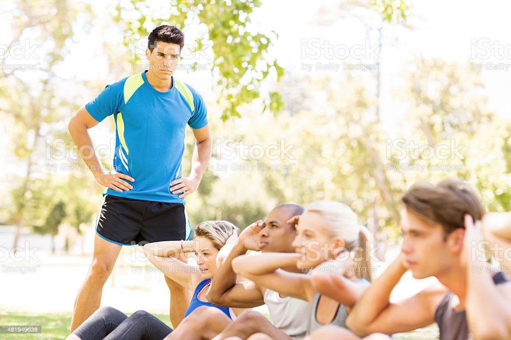 Fitness Trainer Looking At People Doing Sit-Ups In Park stock photo