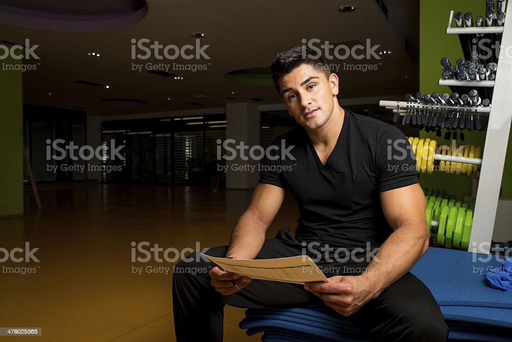 Fitness Trainer looking concerned over papers royalty-free stock photo