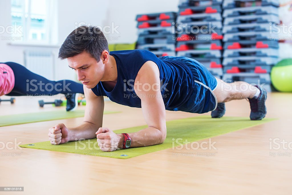 Fitness training athletic sporty man doing plank exercise in gym stock photo