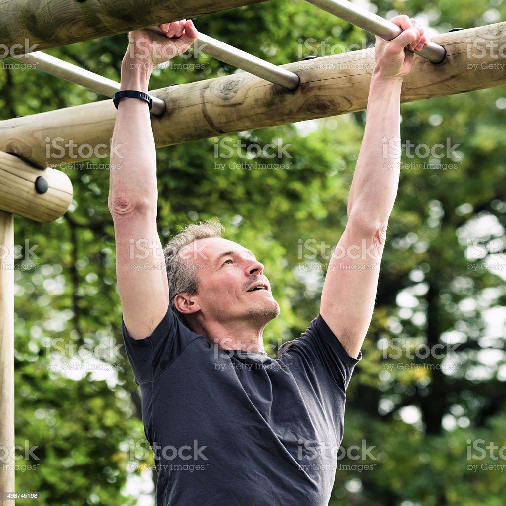 Fitness training on outdoor monkey-bars stock photo
