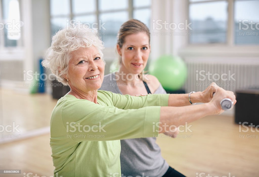 Fitness training with a personal trainer at gym stock photo