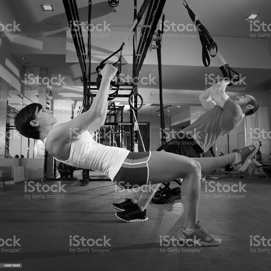 Fitness TRX training exercises at gym woman and man royalty-free stock photo