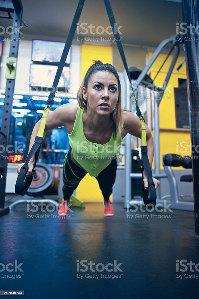 Fitness TRX training exercises at gym woman stock photo