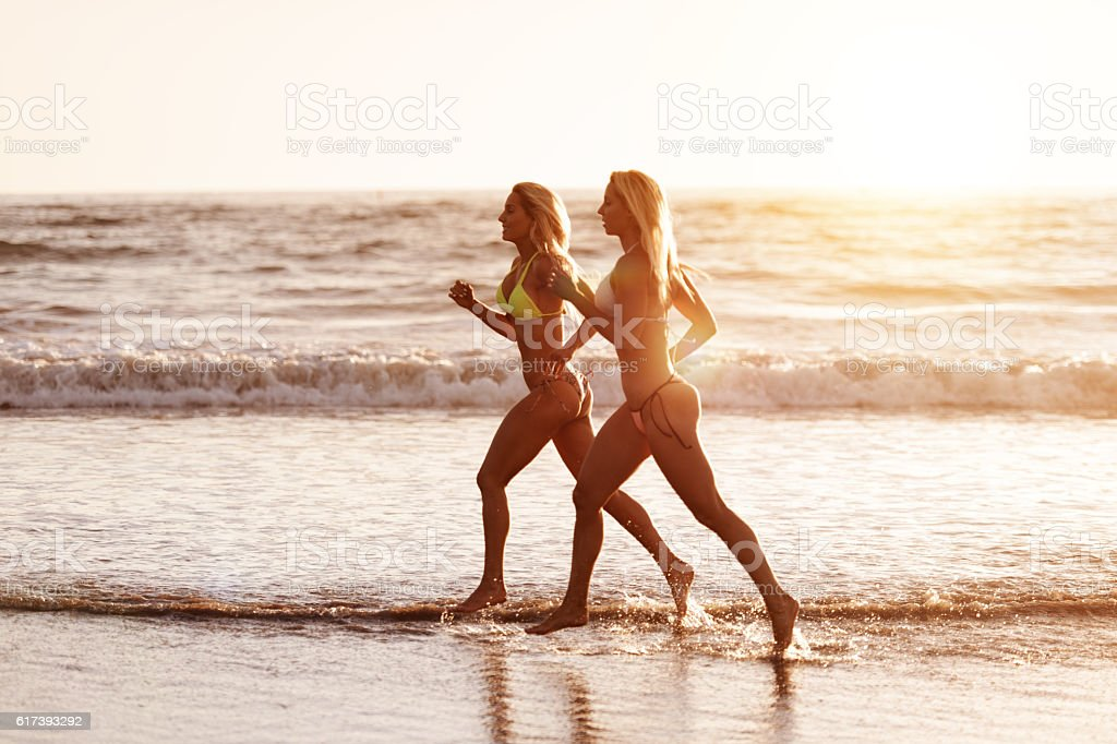 Fitness Twins running on the beach stock photo