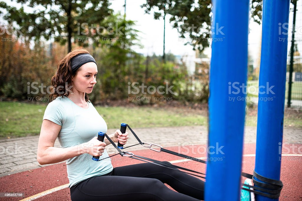 Fitness using trx equipment for fitness in the park stock photo