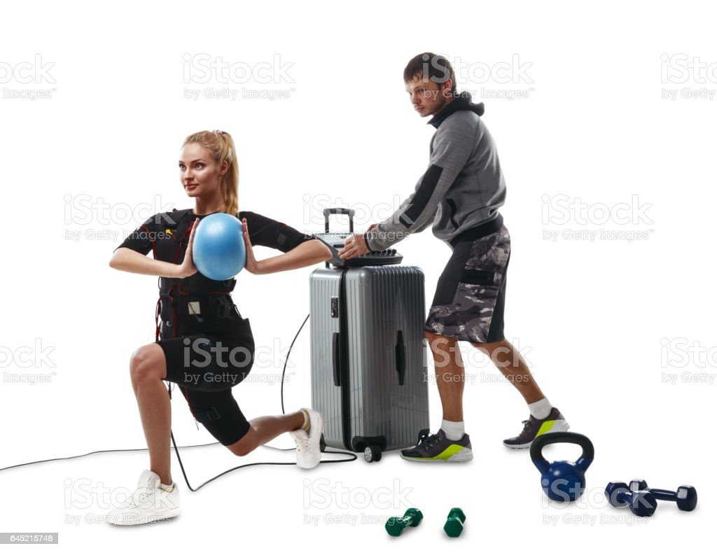 EMS fitness woman doing ball exercises with coach stock photo