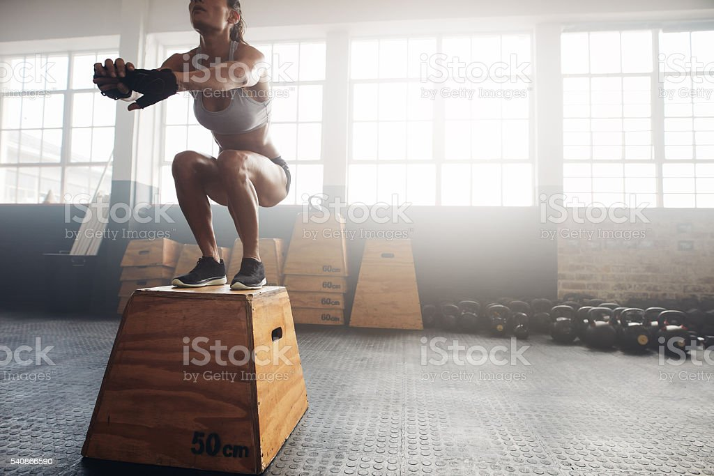 Fitness woman doing box jump workout at gym stock photo