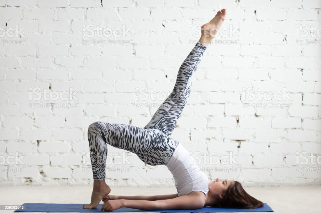 Fitness woman doing one legged bridge pose stock photo