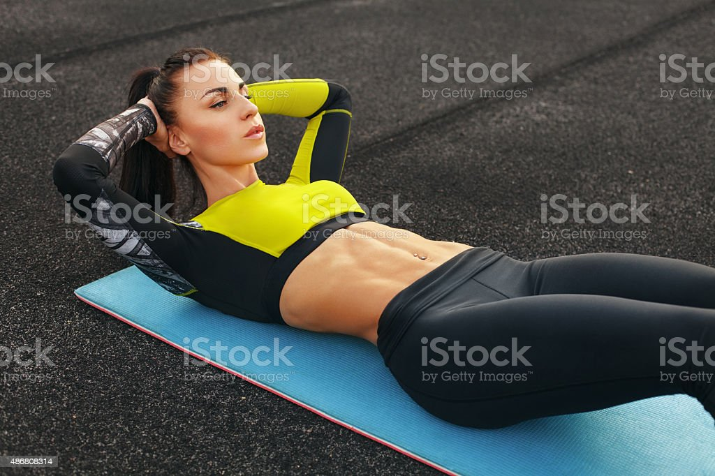 Fitness woman doing sit ups working out. girl exercising abdominals stock photo
