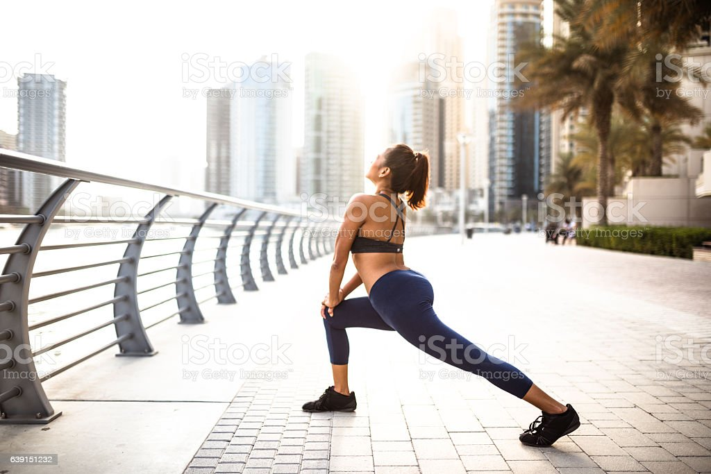 fitness woman doing stretching in dubai marina stock photo