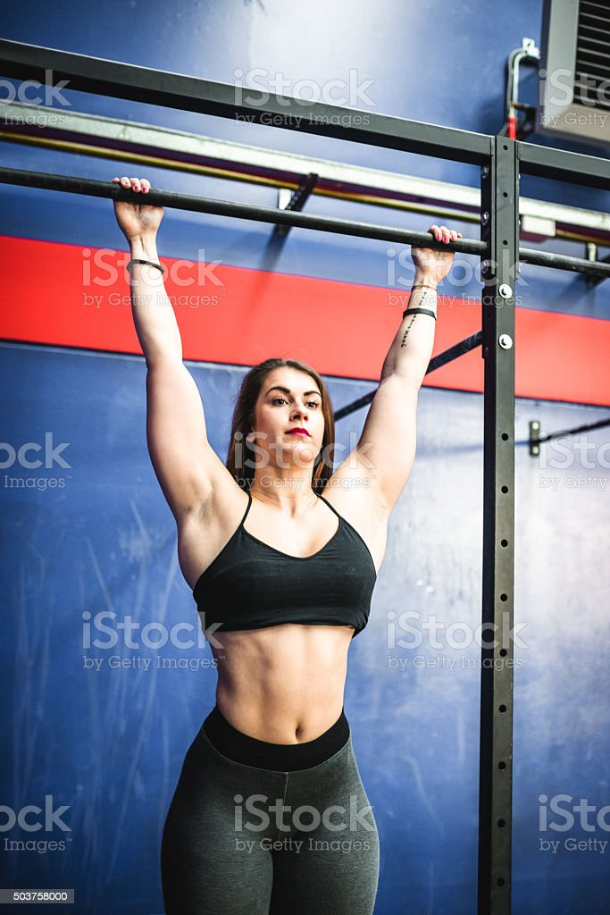 Fitness woman doing traction at the bar in a gym stock photo