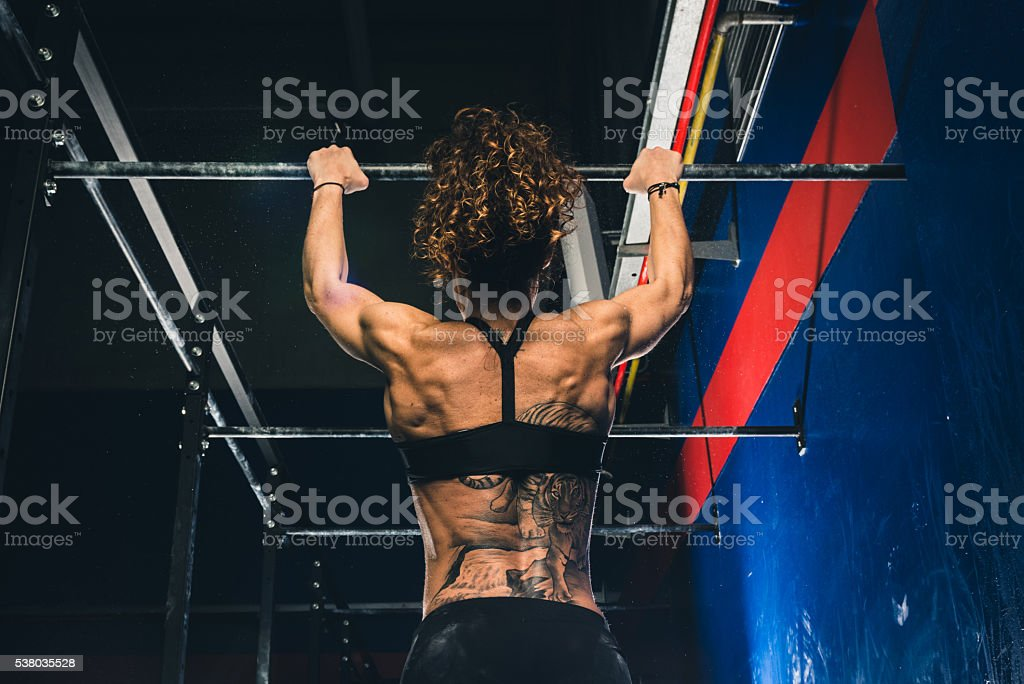 Fitness woman doing traction at the bar stock photo