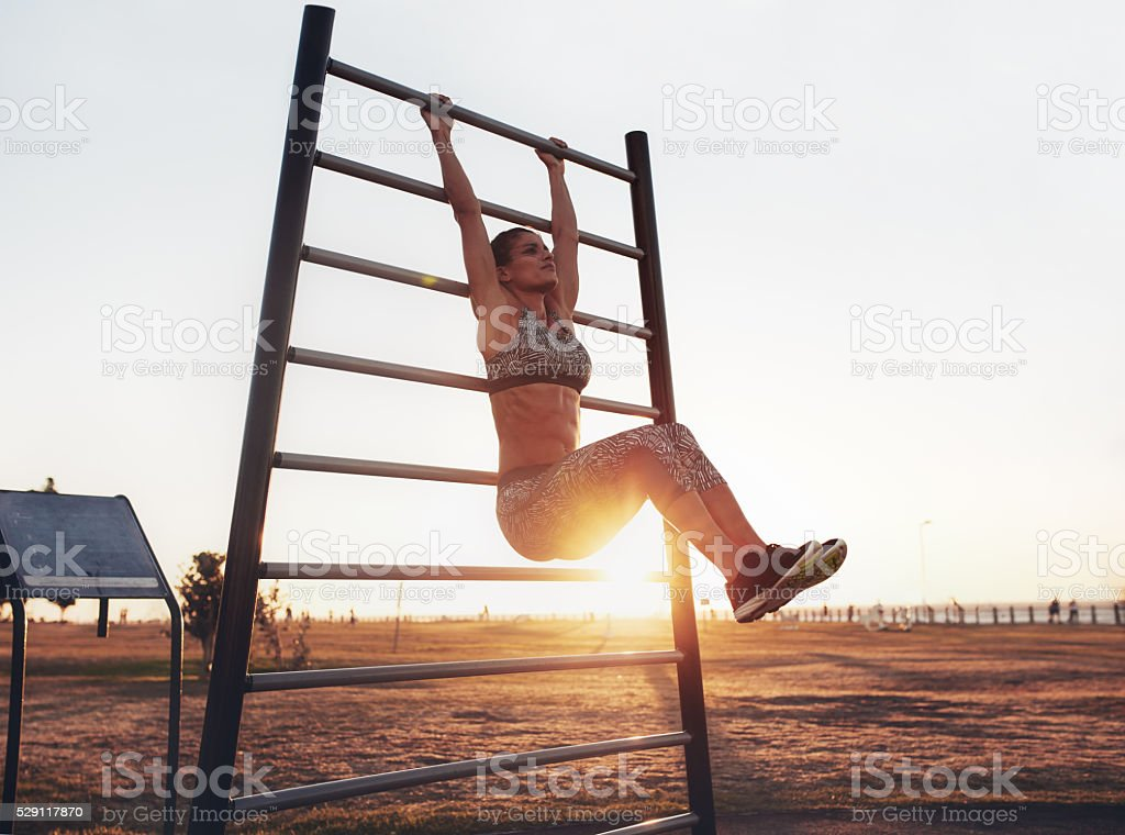 Fitness woman exercising on wall bars outdoors stock photo