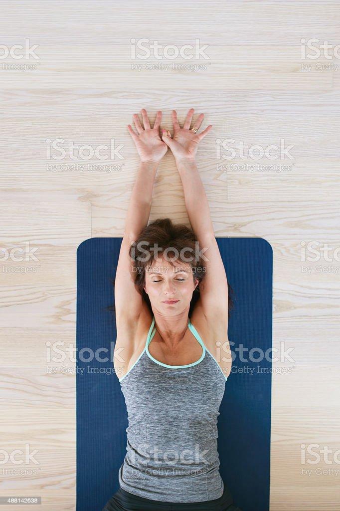 Fitness woman exercising on yoga mat stock photo