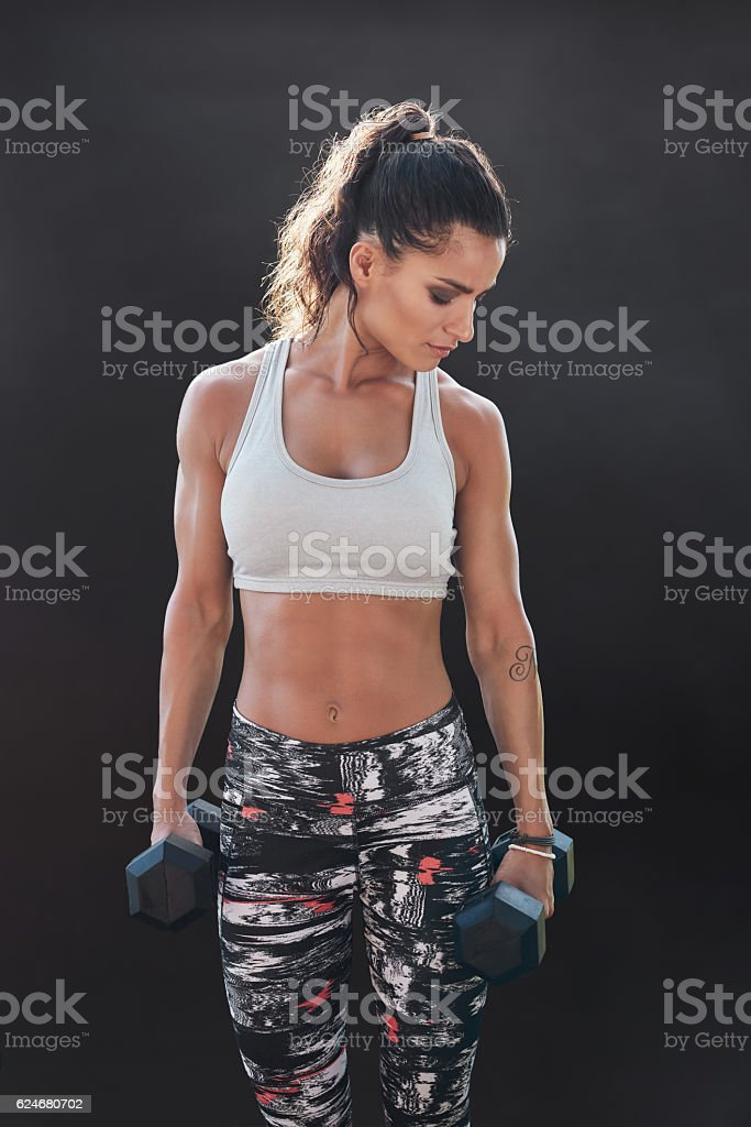 Fitness woman exercising with dumbbells stock photo