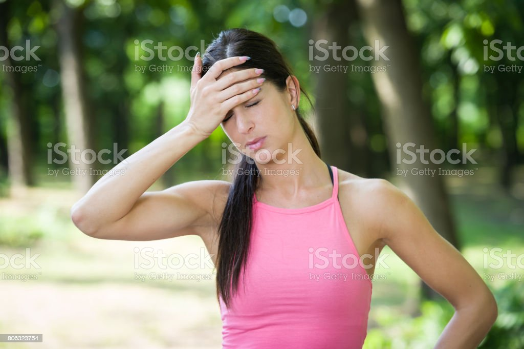 fitness woman headache in a park stock photo