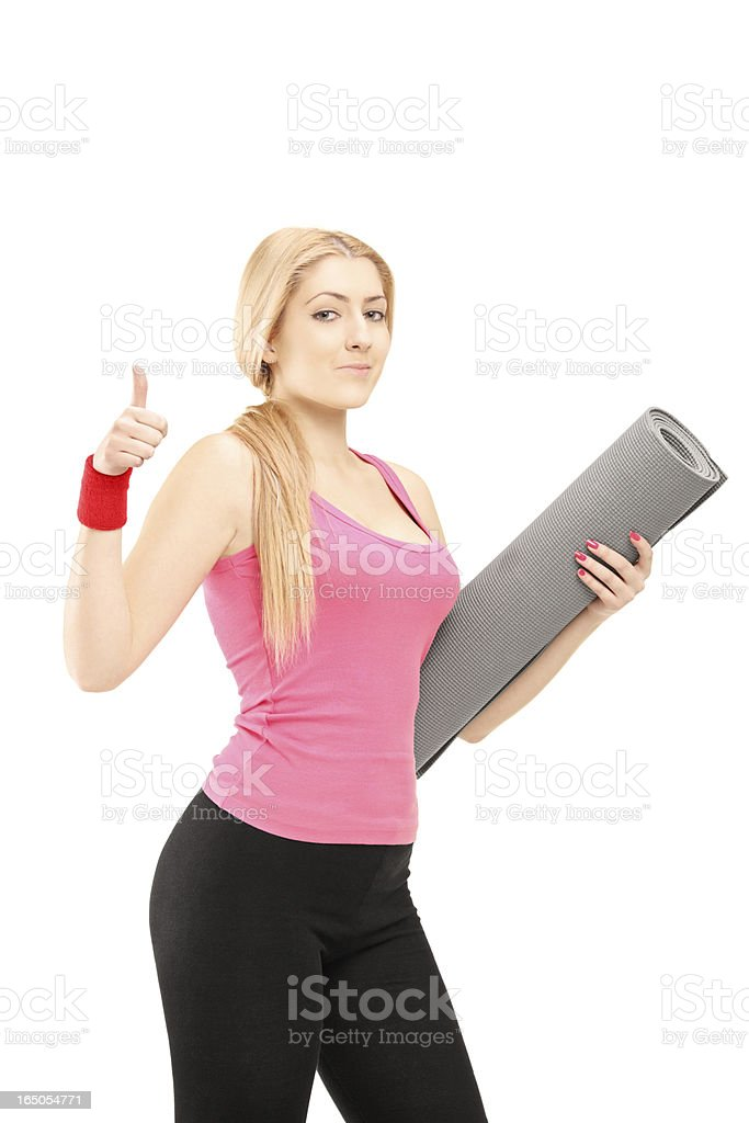 Fitness woman holding a mat and giving thumb up royalty-free stock photo