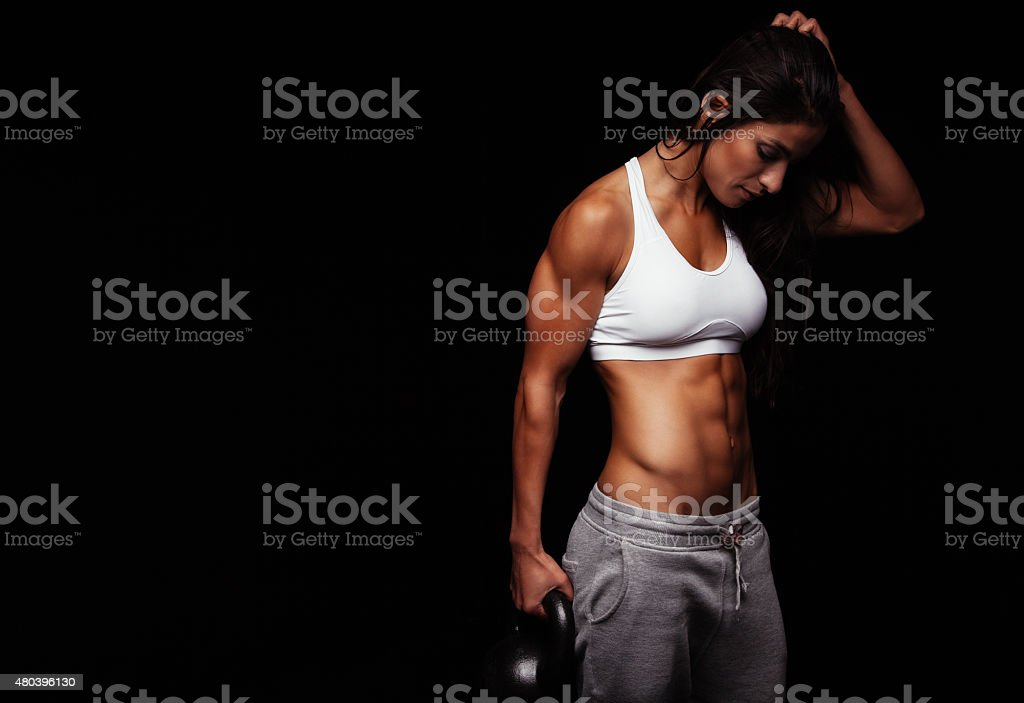 Fitness woman holding heavy kettle bell stock photo