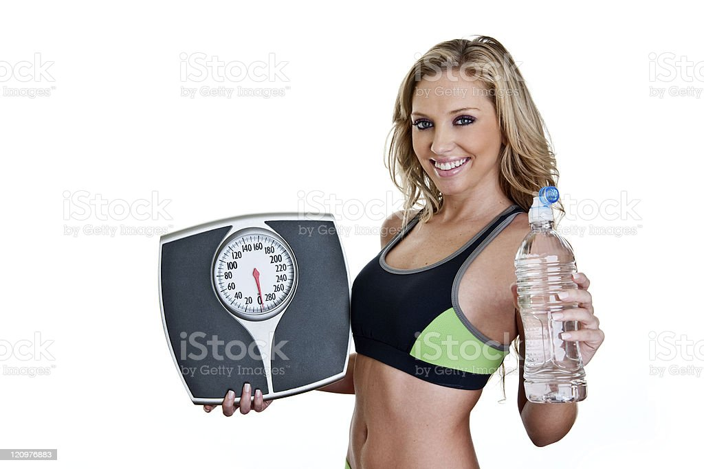 Fitness woman holding scale and water bottle royalty-free stock photo