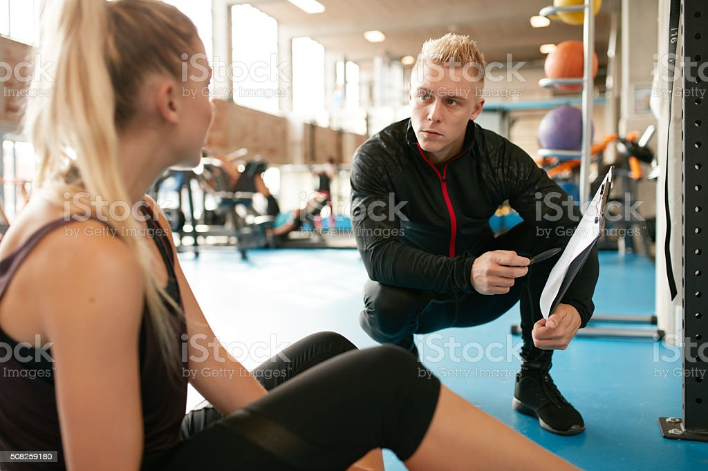 Fitness woman in a gym with personal trainer stock photo