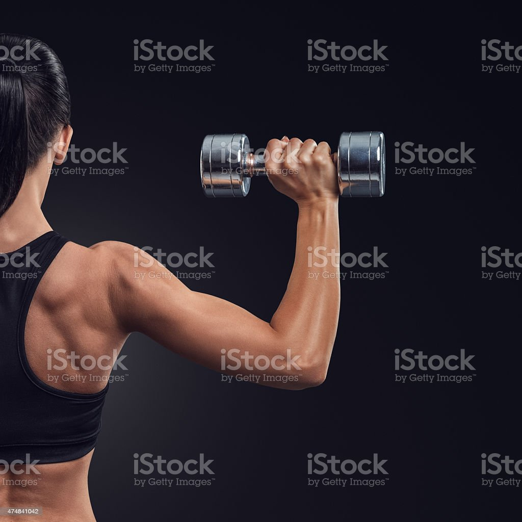 Fitness woman in training muscles of the back with dumbbells stock photo