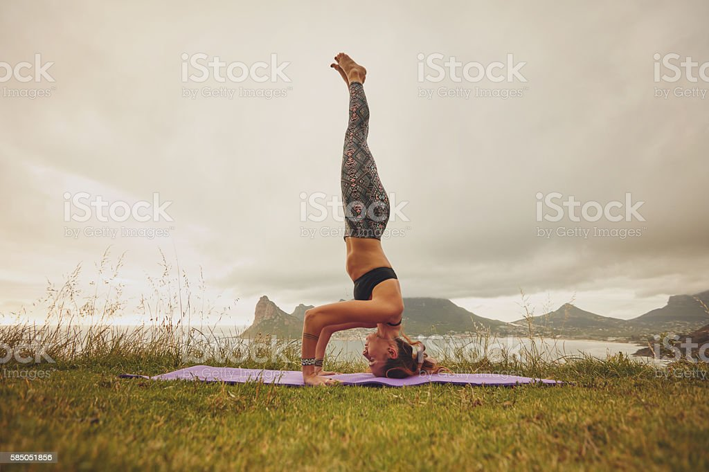 Fitness woman practicing headstand yoga outdoors stock photo