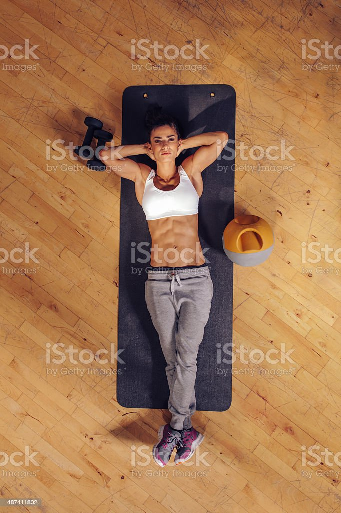 Fitness woman relaxing on yoga mat stock photo