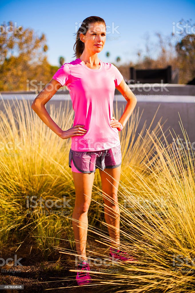 Fitness woman rests with hands on hips in brush stock photo