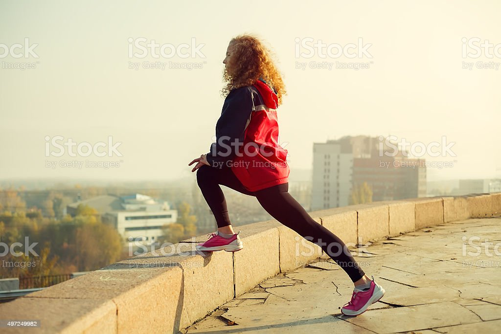 Fitness woman runner relaxing after city running stock photo