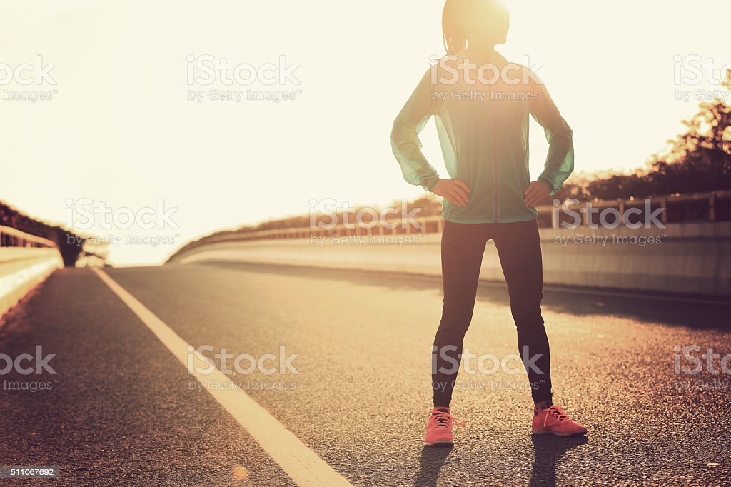 fitness  woman runner standing with her hands on hips stock photo