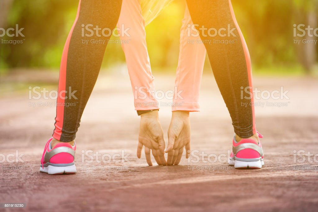Fitness woman runner stretching before jogging stock photo