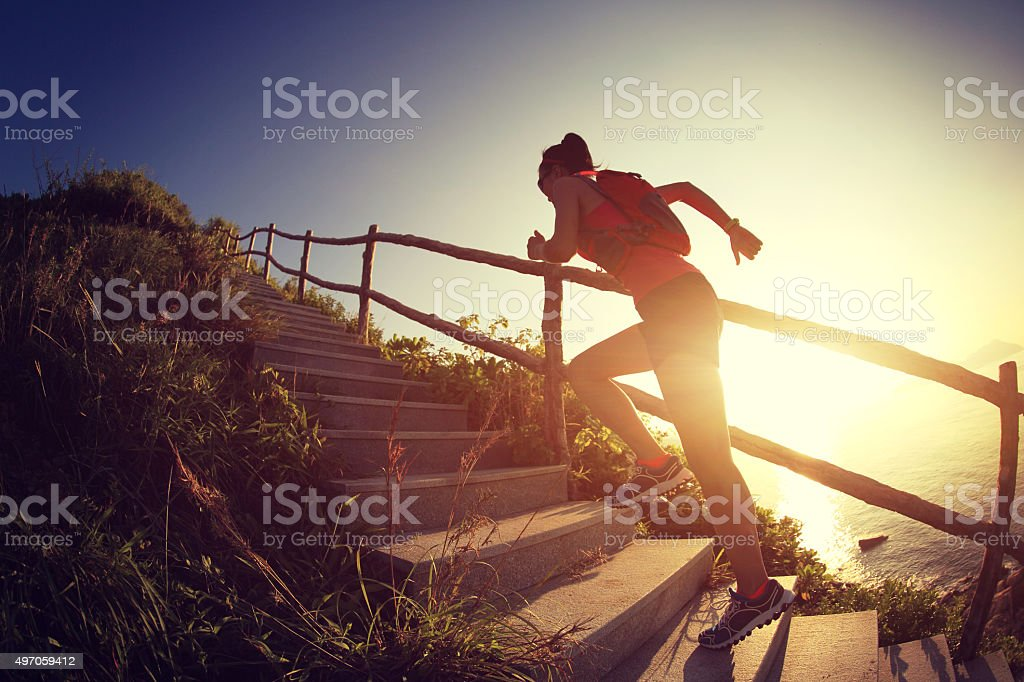 fitness woman runner trail running on seaside mountain stairs, stock photo