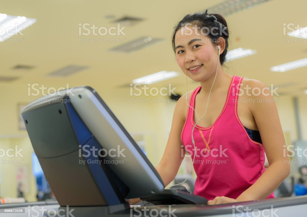 Fitness woman running on treadmill at gym stock photo