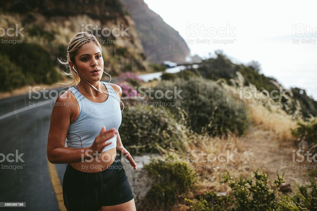 Fitness woman running outdoors in countryside stock photo