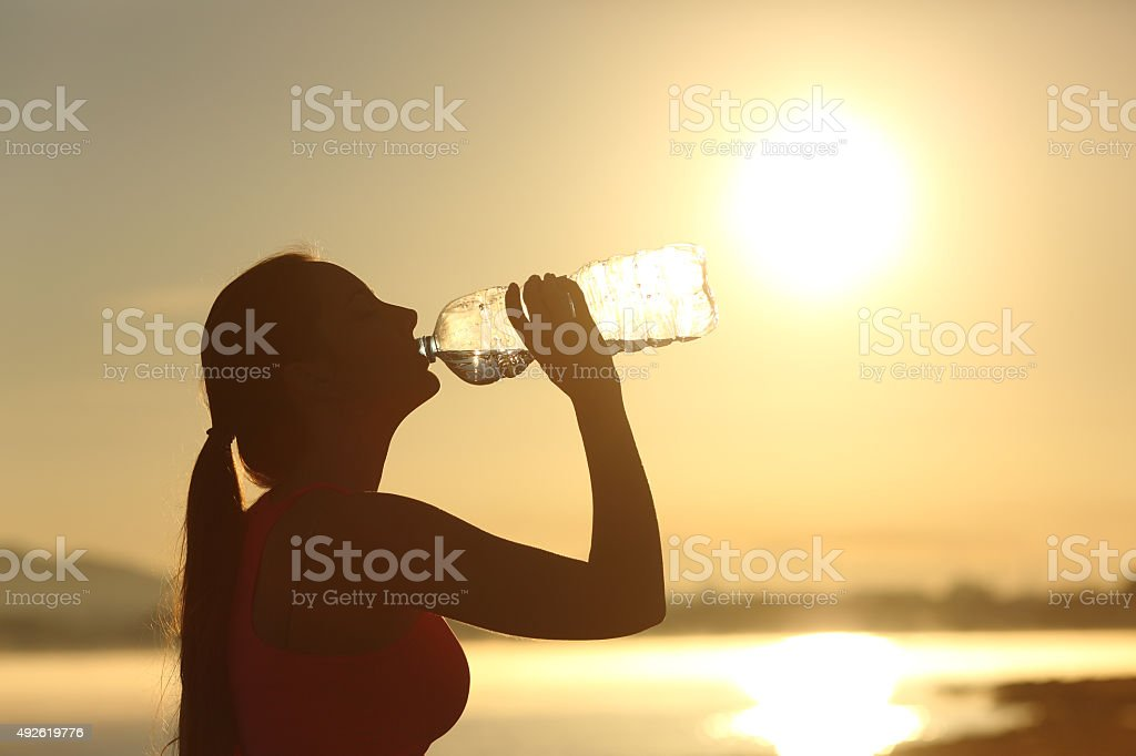 Fitness woman silhouette drinking water from a bottle stock photo
