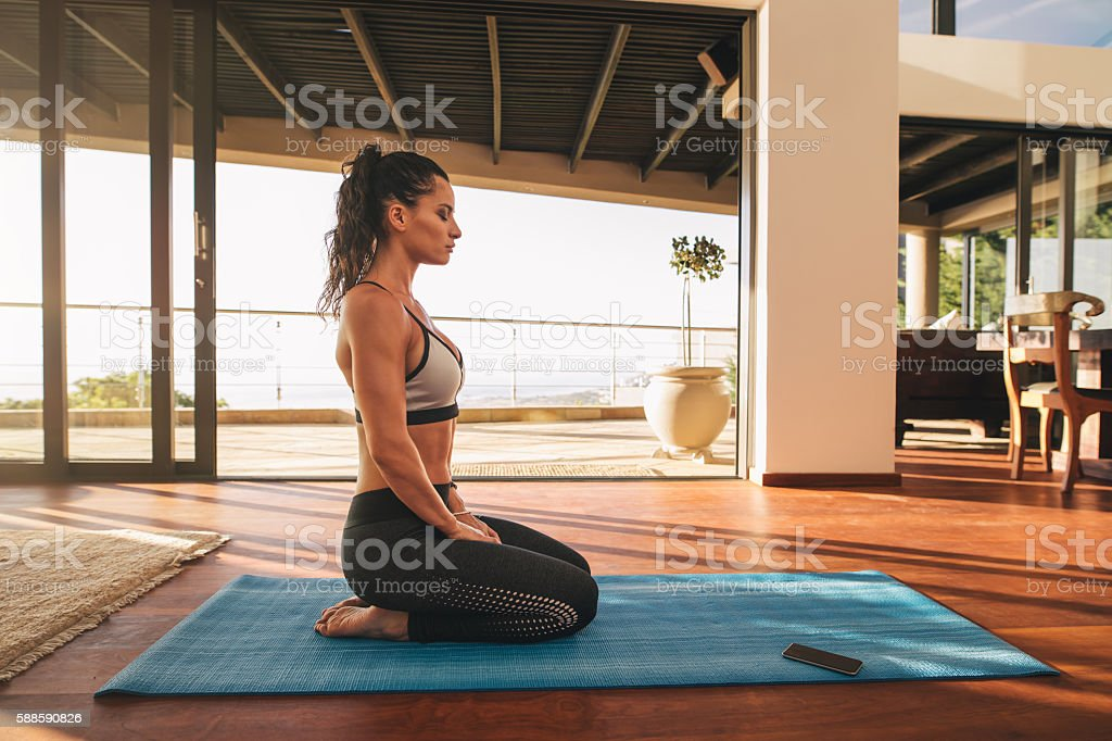 Fitness woman sitting in yoga pose at home stock photo