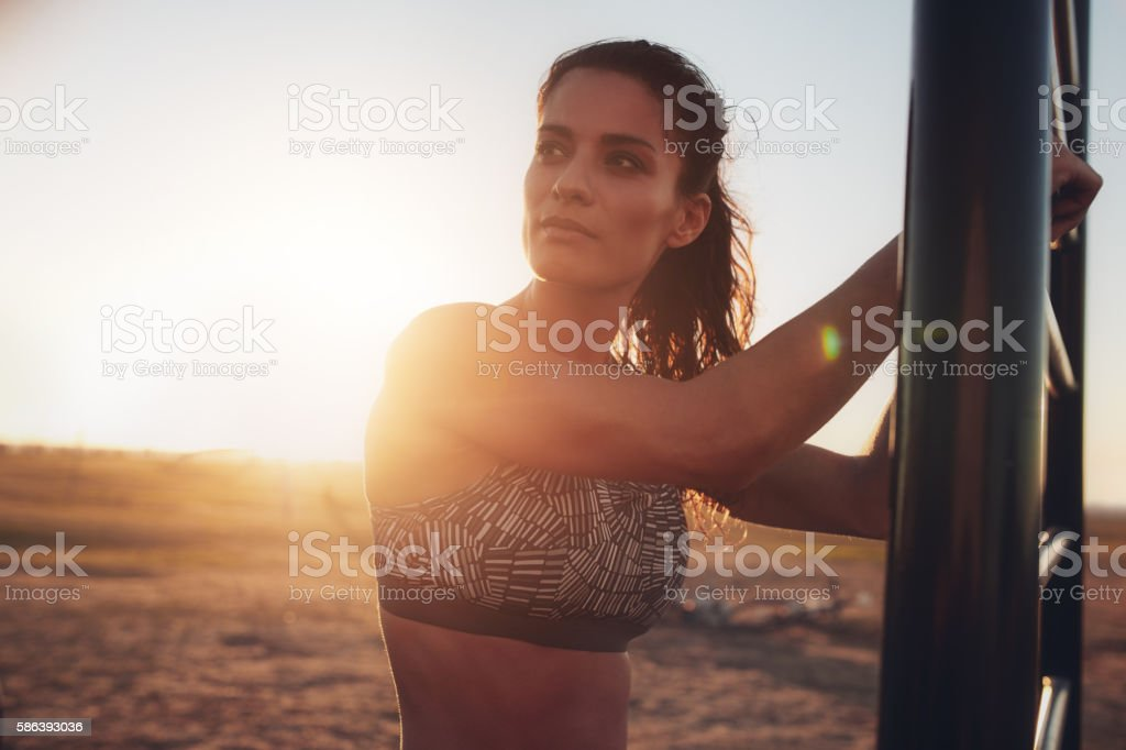 Fitness woman standing outdoors and looking away stock photo