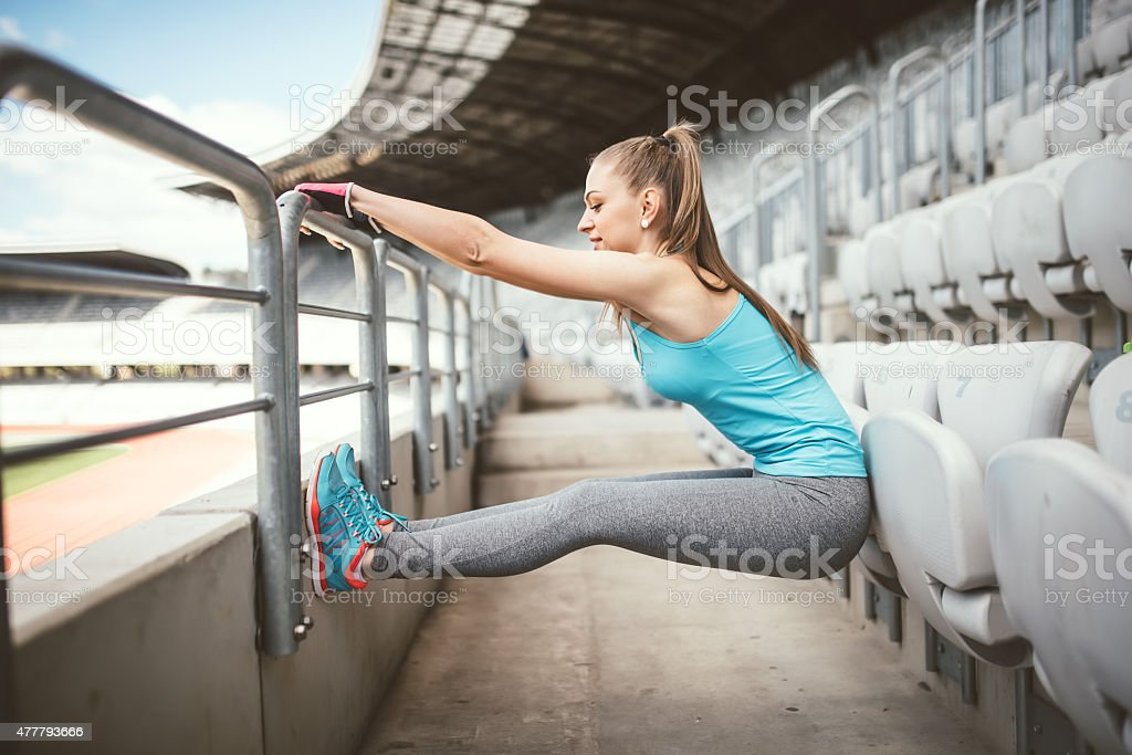 Fitness woman stretching outddors, doing gymnastics excercises and warming up stock photo