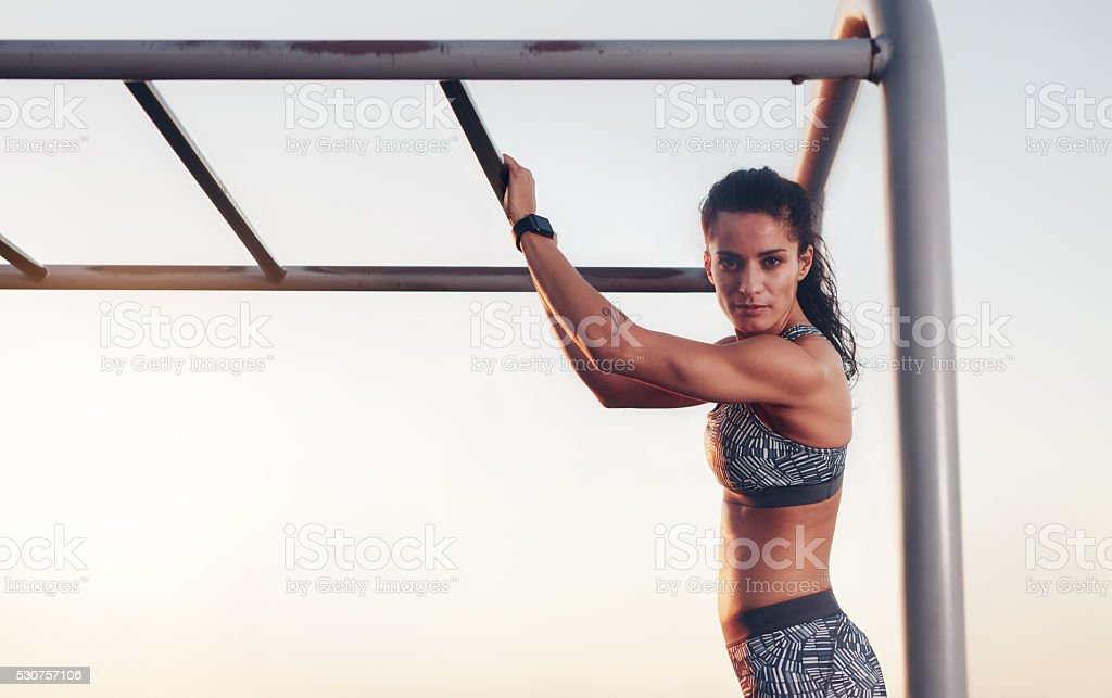 Fitness woman training outdoors on monkey bars stock photo
