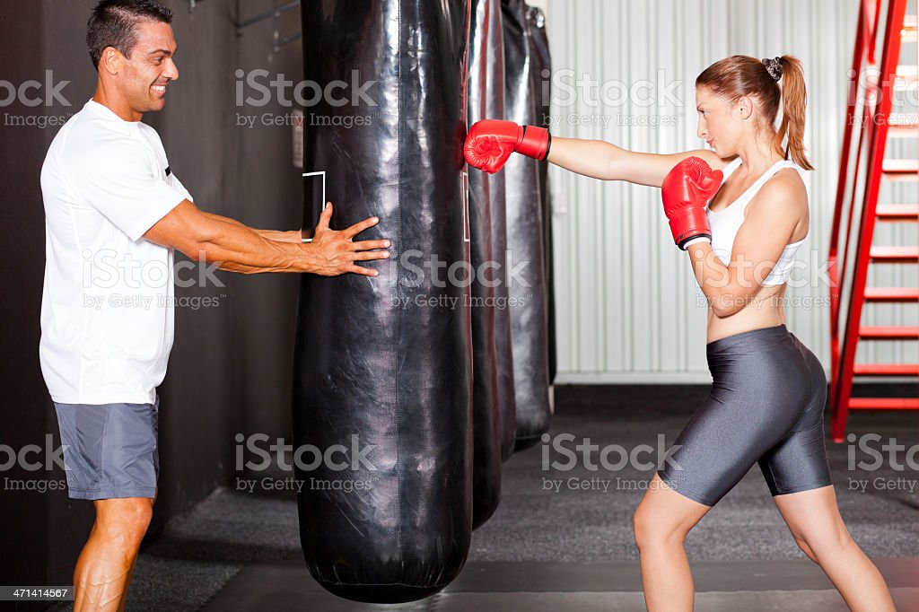 fitness woman training with punch bag in gym stock photo