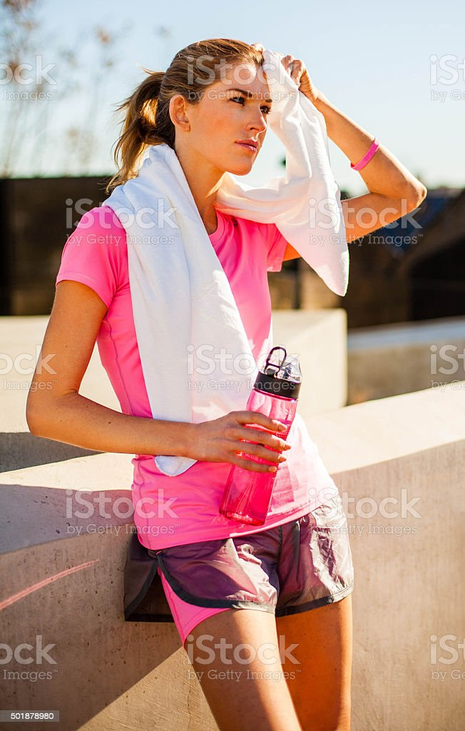 Fitness woman wipes away face with towel stock photo